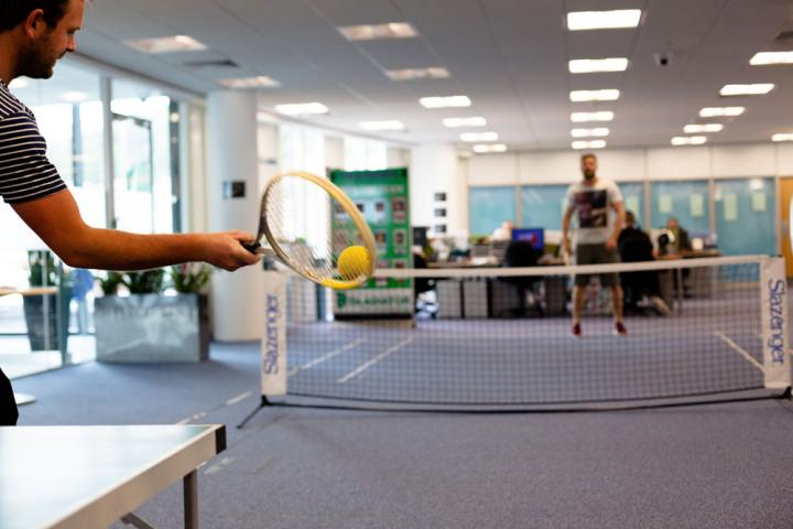 Staff play a game of office tennis